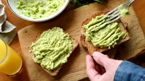 Making avocado toast. Man spread avocado on toasted sandwich bread. Top view