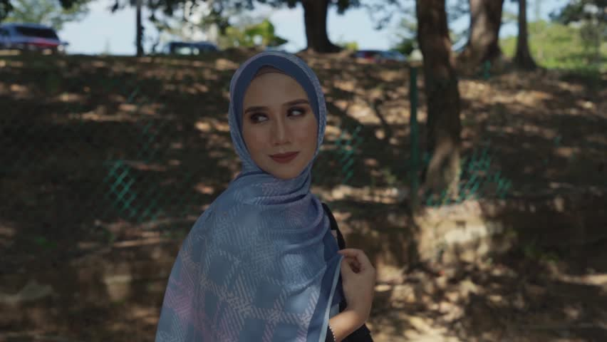 Young Muslim woman in hijab, modern contemporary fashion at park in slow motion. | Shutterstock HD Video #1026716759