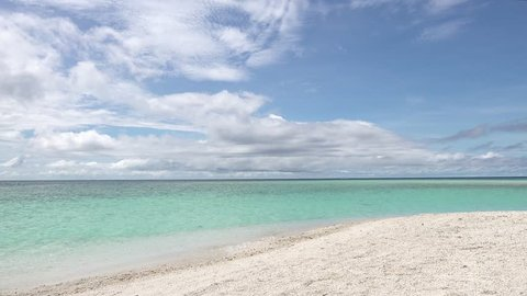 beautiful blue ocean water with waves gently washing ashore on a white sandy tropical beach under a blue sky with fluffy clouds in the Philippines.