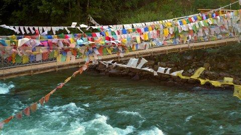 Suspension bridge covered in prayer flags near Paro, Bhutan