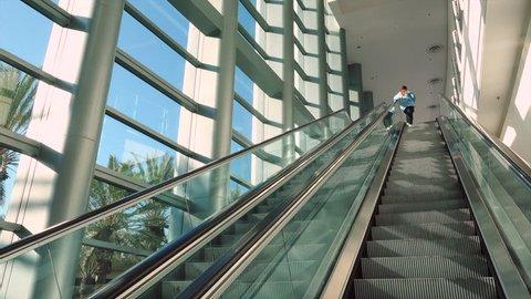 Anaheim, CA / USA - March 30, 2019: Person going up escalator inside the Anaheim Convention Center
