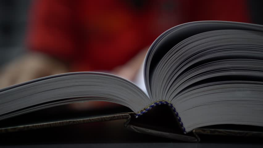 Reading book and education learning concept : Young man opening textbook for reading or searching information in knowledge. | Shutterstock HD Video #1026822239