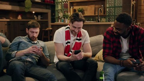 Multiracial group of friends looking at phone screen with smile while sitting on sofa by the tv. Close up diverse multiracial people sitting on couch using smartphones, addiction concept