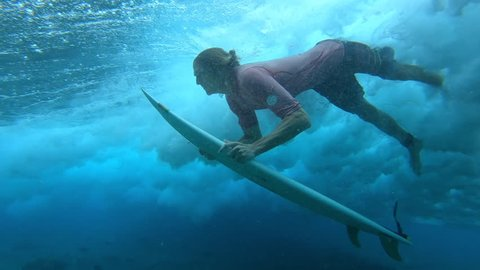 Young male surfer makes dive with his surfboard to safely pass the ocean wave