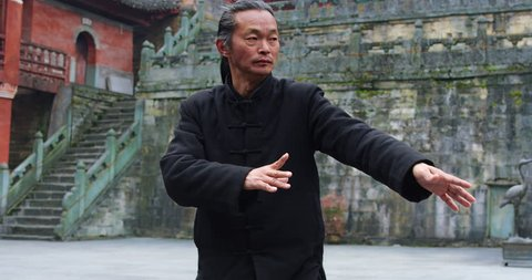 Close up: Asian master, demonstrates Tai chi martial arts in Wudang mountain China. Slow motion, red cinema camera. Note: Chinese symbols, Taoism, practice has a purpose don't forget core belief.