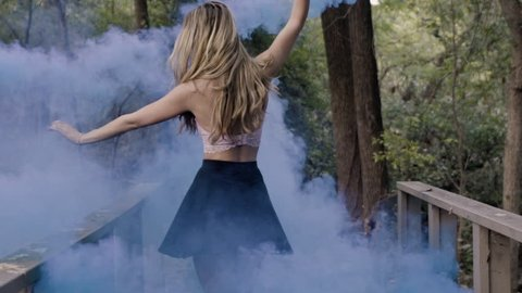 Beautiful ballet dancer twirling and dancing with a smoke bomb in her hand in a forest.