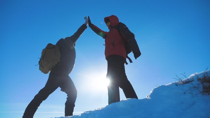 teamwork winners tourists winter snow business travel trip met on top of a mountain. two men with backpacks hiking met in the silhouette in mountains with sunlight. slow motion video. rock lifestyle