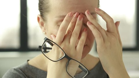 Feeling tired and stressed. Frustrated young woman keeping eyes closed and massaging nose while sitting at her working place in office. Young Businesswoman is tired and feels stressed out.