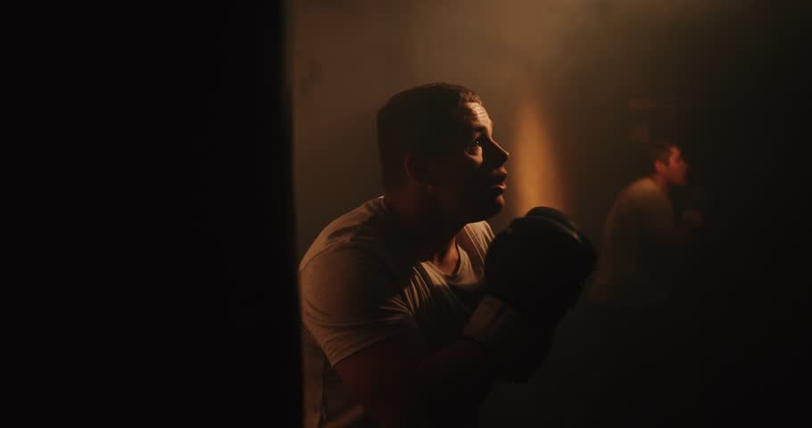 Close-up of aboxer at the moment of impact on punching bag over black background in dark room with rare sunlight. Drama, 4k. Sport #1026909359