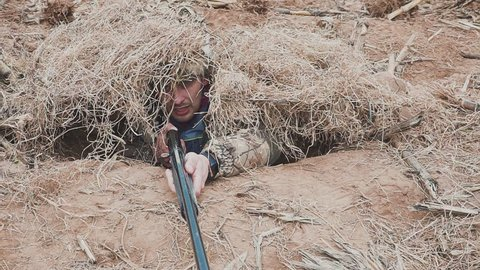 Goose Hunter hiding in the dry grass with a hunting rifle in his hands