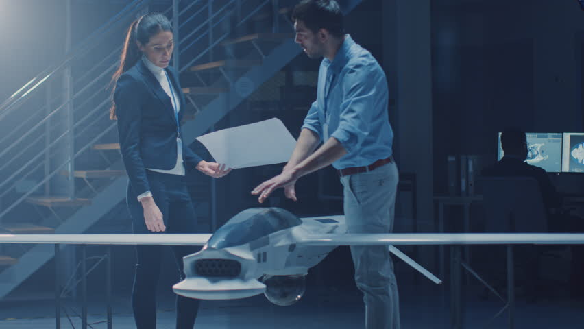 Two Aerospace Engineers Work On Unmanned Aerial Vehicle / Drone Prototype. Aviation Scientists Talking, using Blueprints. Industrial Laboratory with Commercial Aerial Surveillance Aircraft | Shutterstock HD Video #1026990629