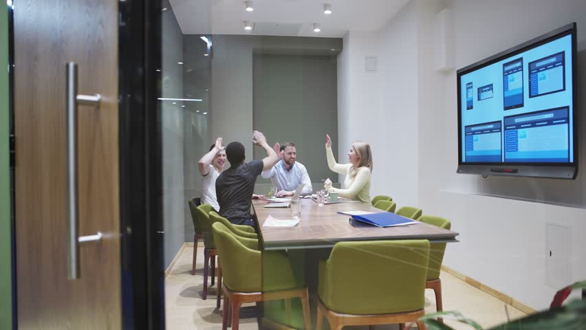 Tracking shot of creative team brainstorming in meeting room behind glass wall. Ecstatic business people giving high fives after generating good idea  #1026994049