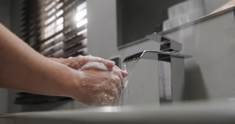 Young people and body care. Person rinsing hands in modern design bathroom at home. Man washing male hand with soap and water under faucet in hotel room during travel. Slow motion | Shutterstock HD Video #1026997499