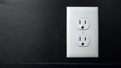 Male hand plugs in and unplugs a two pronged cord into the bottom outlet of an American electrical socket Copy Space Left