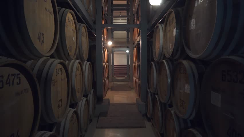 Barrels of cognac, wine or whiskey. Extract of brandy in oak barrels. Alcohol warehouse. Hundreds of barrels in an underground vault. Camera movement between barrels. | Shutterstock HD Video #1027016909