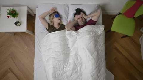 Annoyed man cannot sleep because of noise of wife snoring in bedroom at home. Young couple has problem with woman's snoring.