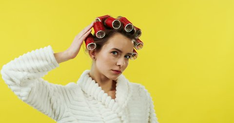 Caucasian young woman in the white bathing robe and curlers comingin the shot on the yellow wall and fixing her clothes and hair.
