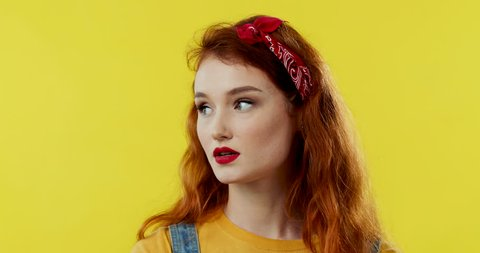 Close up of the caucasian young attractive red-haired girl on the yellow back wall looking unsatisfied, bored and tired. Portrait.