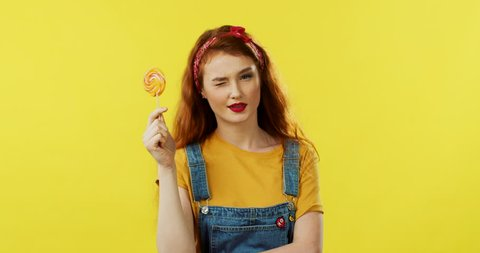 Beautiful and stylish young caucasian girl, flirty coquette, smiling cheerfully and holding a lollipop and hiding her eyes over it. Yellow wall on the back.