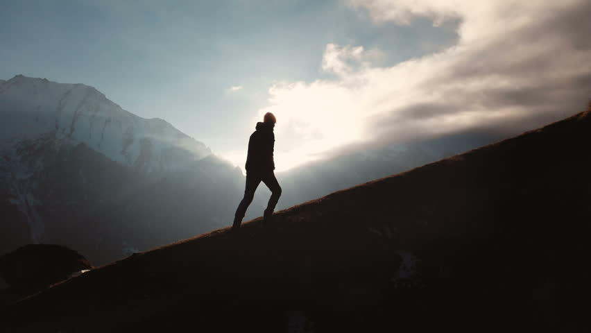 Very long shot Aerial view of epic shot of a man walking on the edge of the mountain as a silhouette in a beautiful sunset. Silhouette of a man with a beard and wearing a hat climbing uphill #1027098119