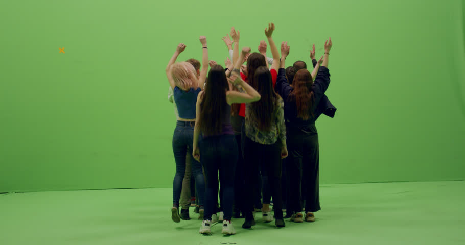 GREEN SCREEN CHROMA KEY Back view group of young people dancing and jumping with hands in the air. 4K UHD ProRes 4444