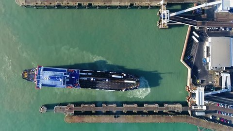 Aerial top down view of ferry docking at port these are merchant vessels used to carry passengers vehicles and cargo and form a part of public transport systems of many waterside cities and islands 4k