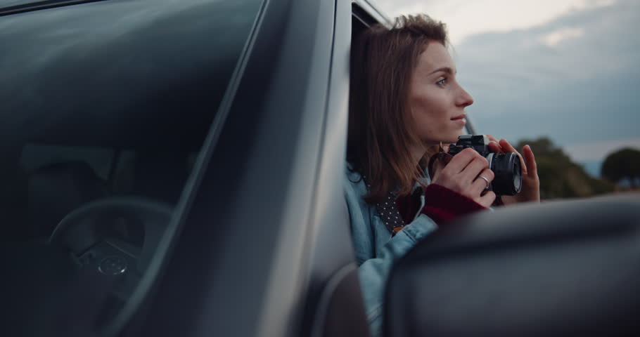 Young hipster girl traveling in car exploring Europe, attractive female traveller taking photos of sunset on camera while sitting in an off-road car, slow motion, shot on cine camera 4K | Shutterstock HD Video #1027149839