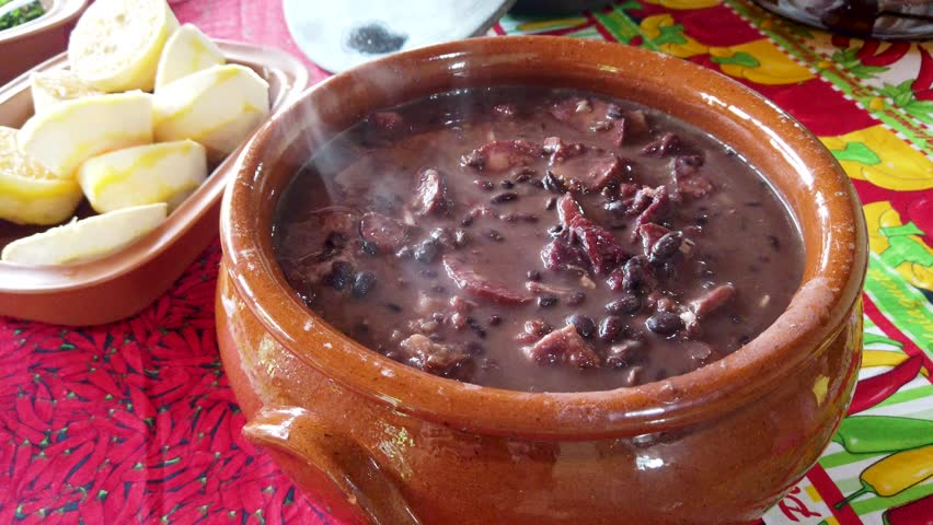 Tradicional brazilian feijoada pan served in a clay pot with smoke, stable  close up