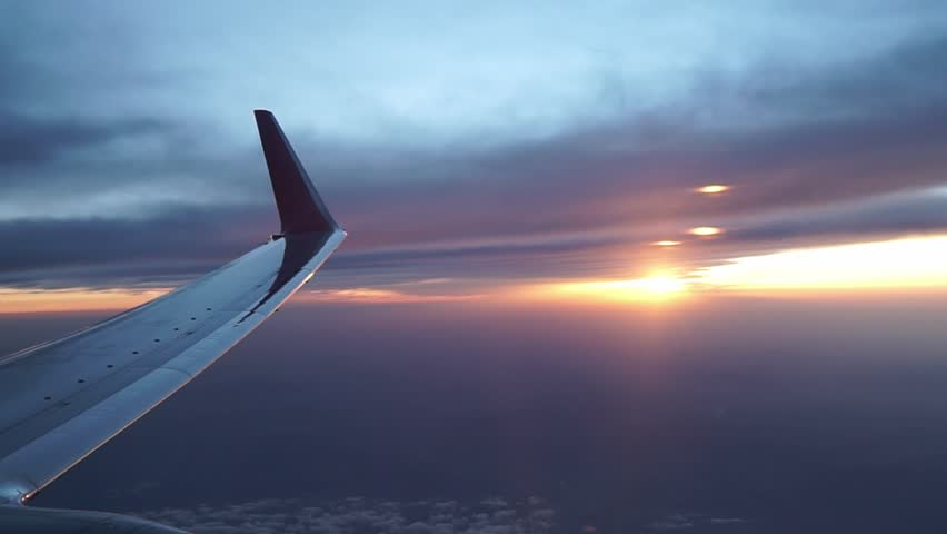 View of a sunset through the window of the plane flying. #1027173569