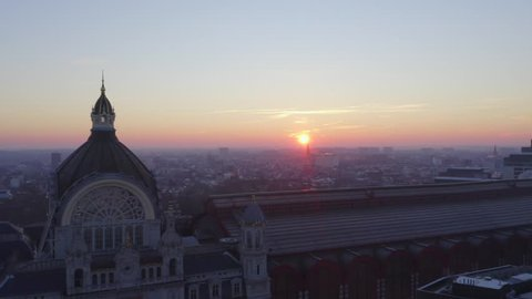 Video shows the beautiful train station in Antwerp with sunrise background. The sky orange sky turn the station into golden color. The station is the most beautiful station in world.