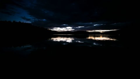 Starlapse on tranquil lake with Moving Clouds and Moonlight