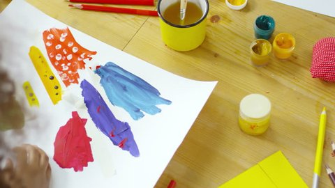 Top view of little girl taking off adhesive paper tape from gouache painting while making creative