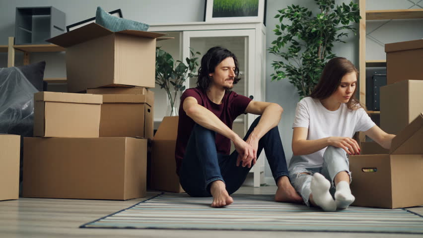 Cheerful girl and guy are unpacking during relocation taking things from box and talking sitting on floor in new house. Household and relationship concept. | Shutterstock HD Video #1027227119