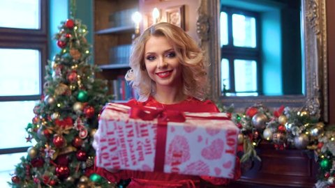 Beautiful blonde girl holding out a gift box on the background of a decorated Christmas tree. The concept of new year holidays