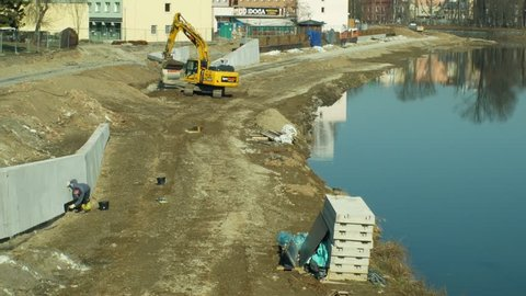 OLOMOUC, CZECH REPUBLIC, JANUARY 30, 2019: Building flood protection on the Morava River in Olomouc, excavator and digger increases the river bank capacity for water, regulated and regulation