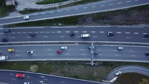 Car traffic on freeway drone aerial top down view footage, vehicles driving on highway road with ramp lanes, 4K video of transportation from above