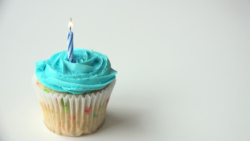 One cupcake frosted with blue icing and a blue birthday ...