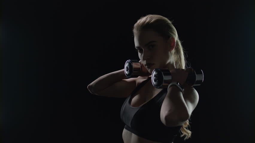 Fit girl posing with dumbbells on shoulders in studio. Sport woman silhouette after dumbell workout in gym. Athlete model portrait with fitness dumbbells on black background. Sport motivation | Shutterstock HD Video #1027282949