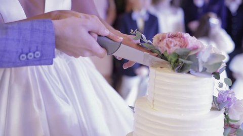 Brides cut wedding cake. A bride and a groom is cutting their wedding cake. Hands of bride and groom cut of a slice of a wedding cake. Slow motion