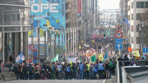 Brussels, Belgium - March 30, 2019:Striking view of a huge squash of green-conscious people bringing multicolored banners and flags in a city street in Belgium on a sunny day in spring