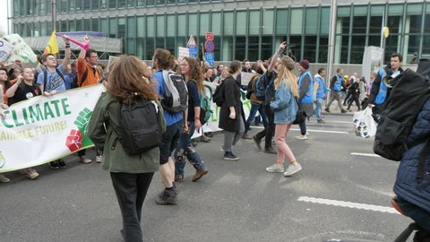 Brussels, Belgium - March 30, 2019:Optimistic view of thousands of young people with a wide banner Student 4 climate marching, chanting and dancing in a street in Belgium in spring