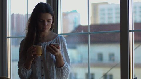 Attractive girl holding cellular mobile phone drinking morning coffee tea at home natural light. Young woman typing mobile smart phone sitting at windowsill indoors 4k. happy modern lifestyle gadget