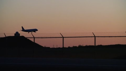 Extreme long shot panning to follow a commercial airplane landing on a runway at dusk