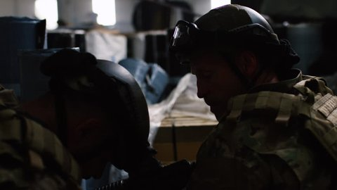 Over the shoulder shot of special ops military SWAT team members crouched down taking out bad guys in warehouse under dramatic daytime lighting. Daytime medium close on RED camera.