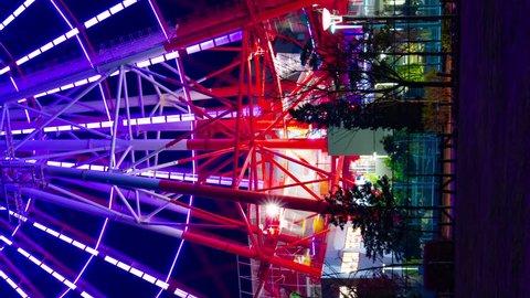 Time lapse ferris wheel at the amusement park at night vertical shot. Koutou-ku Odaiba Tokyo Japan - 01.08.2019 : It s a ferris wheel at night. camera : Canon EOS 5D mark4