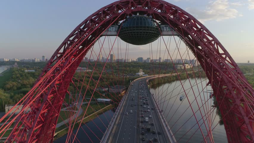 Aerial photography/ drone shooting: cable-Stayed car bridge with a red metal arch over the river at sunset, heavy traffic, the camera flies under the arch over the highway. Picturesque Bridge | Shutterstock HD Video #1027436669