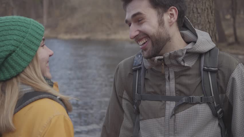 Portrait of the young couple of tourists standing on the river bank with backpacks on their backs. Bearded man and pretty woman in yellow jacket talking and laughing. Lovers rest outdoors