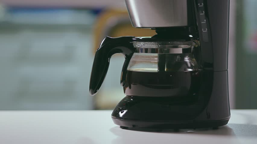 Employee pouring coffee from a bowl into a mug. Black filter coffee at the office. 4k | Shutterstock HD Video #1027454729