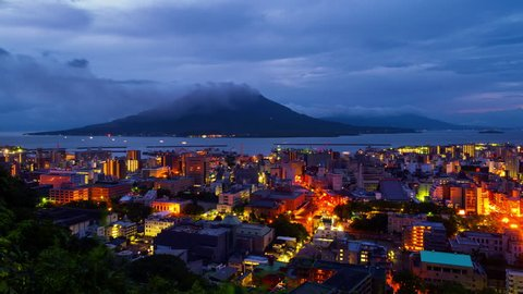 Kagoshima, Japan. View of mountain Sakurajima an active volcano. Aerial view of Kagoshima city in Japan at sunrise. Time-lapse with volcano eruption in the morning
