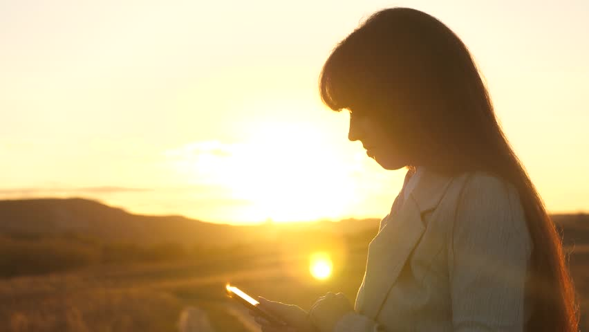 hands of man are driving their fingers over tablet. man checks email. Businessman working on tablet at sunset in park. agronomist works with the tablet in field. farmer on plantation with smartphone. #1027479689